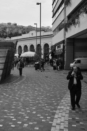 ATHENS GREECE  APRIL 24 2015: Man talking on mobile phone and crowd of people at Monastiraki square under the Acropolis in downtown Athens Greece.