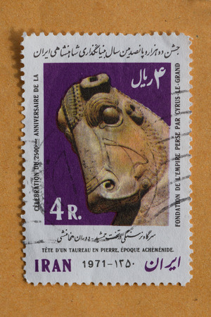 cyrus: IRAN  CIRCA 1971: Bull head on stone ancient art from the Achaemenid era on vintage postage stamp printed by the Iranian Post to commemorate the 2500th anniversary of the establishment of the persian empire by Cyrus the Great.