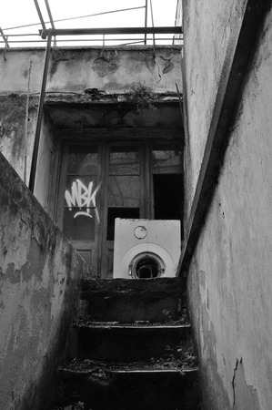 urban decline: Basement stairs and abandoned house exterior with broken washing machine on rainy day. Black and white. Stock Photo