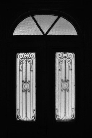 arched: Vintage door frame with decorative motif and arched glass lite. Abandoned neoclassical house dark interior black and white.
