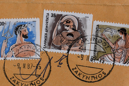 postmarked: GREECE  CIRCA 1986: Poseidon ancient greek god of the sea Athena goddess of wisdom and Hestia goddess of home and family values mythology illustrations on vintage postage stamps printed and postmarked by the Hellenic Post.