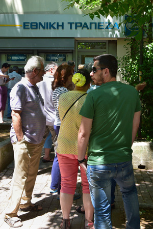 ATHENS, GREECE - JULY 1, 2015: People queuing at Ethniki bank branch to withdraw cash money from ATM machine cashpoint. Banks are closed to the public and capital controls are implemented as Greece heads for a referendum.