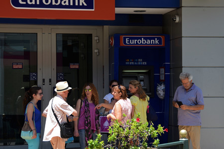 closed society: ATHENS, GREECE - JULY 1, 2015: Group of people waiting at atm machine queue outside a closed greek bank inform a tourist that capital controls are not implemented on credit cards issued abroad and there is no daily cash limit for foreign visitors.