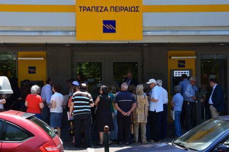 withdraw: ATHENS, GREECE - JULY 1, 2015: Crowd of people queue at Piraeus bank one of the few branches open to the public only for pensioners without ATM cards to withdraw part of their pension in cash money. Third day of capital controls and first after failure to