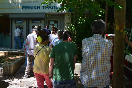 ATHENS, GREECE - JULY 1, 2015: Line of people waiting to withdraw cash money from ATM machine cashpoint. Banks are closed and daily limit capital controls are implemented. First day after Greece defaults on IMF loan payment.