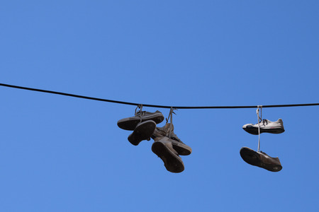 urban culture: Shoe tossing old sneakers footwear with tied shoelaces hanging from a wire. Stock Photo