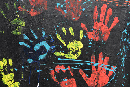 kids hand: Messy handprints and dripping paint on textured wall background. Colorful hand imprints abstract pattern.