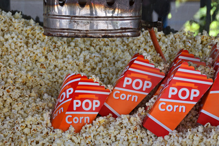 popper: Pile of fresh popcorn and portions in bags made by antique hot air popper machine. Salty snack.