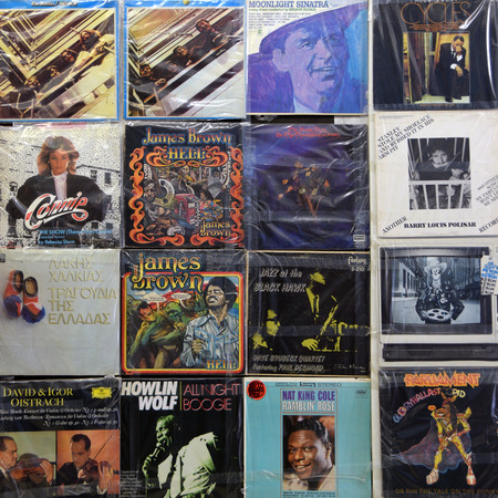 scott: ATHENS, GREECE - APRIL 24, 2015: Wall with vintage vinyl records old lp album covers in plastic sleeves. Music background. Editorial