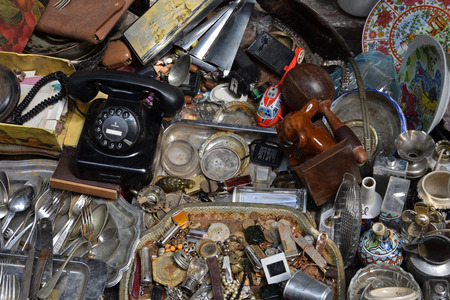 dial plate: ATHENS, GREECE - MAY 21, 2015: Antique objects for sale at flea market. Old rotary dial telephone rusty cutlery vintage porcelain plates and other dusty things.