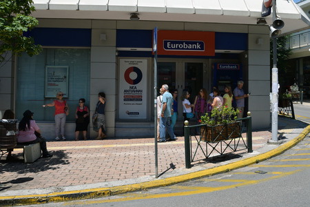 implemented: ATHENS, GREECE - JULY 1, 2015: People patiently waiting at ATM cashpoint queue. Banks are closed and capital controls implemented allow a maximum cash money withdrawal of 60 euro per day. Greek debt crisis.