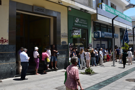 ATHENS, GREECE - JULY 1, 2015: Long queue of people wait for money from ATM cashpoint. Banks are closed after bank run and capital controls implemented allow cash withdrawal of 60 euro per day. Greek financial crisis. Editorial