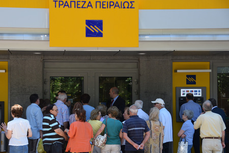 ATHENS, GREECE - JULY 1, 2015: Bank workers assist crowd of people waiting to withdraw part of their pension. Some banks were open to the public today only for pensioners without ATM cards after capital controls were implemented on the 29th of June. 에디토리얼