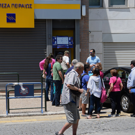 ATHENS, GREECE - JULY 1, 2015: Queue of people waiting for money from ATM cashpoint in front of a closed bank. Capital controls implemented allow a withdrawal of 60 euro per day. Greek government debt crisis.