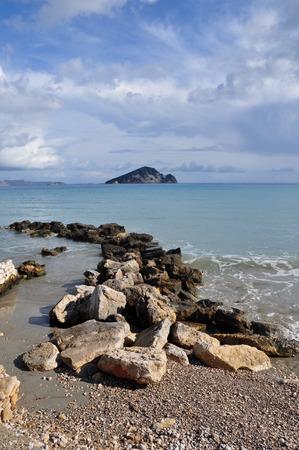 islet: Ionian sea and blue sky horizon breakwater rocks and. View of Marathonisi islet from Keri beach in Zakynthos Greece.