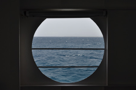 ship porthole: Ship porthole with view to open sea and sky horizon. Abstract background.