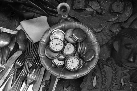 watch groups: ATHENS, GREECE - JUNE 12, 2015: Antique pocket watches and other vintage objects for sale at street market. Black and white.
