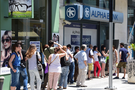 waiting in line: ATHENS, GREECE - JULY 1, 2015: Long line of people waiting to withdraw cash money from ATM cashpoint outside a closed bank. Capital controls during greek financial crisis.