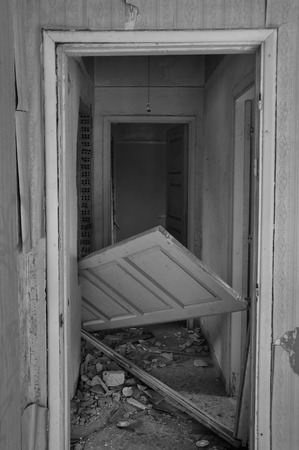 wonky: Abandoned house hallway with unhinged door and rubble on dirty floor. Black and white. Stock Photo