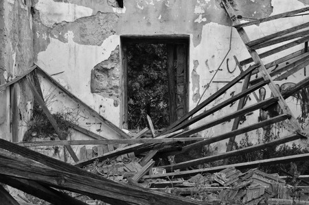 Collapsed roof chipped interior walls and window of an abandoned house. Black and white. Stock Photo