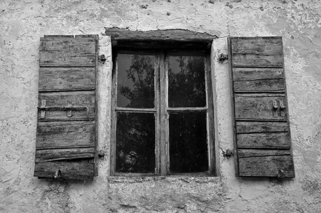 wooden window: Dusty window wooden shutters and textured wall of abandoned house. Black and white.