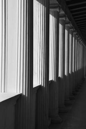 ionic: Light shining through ionic columns abstract architectural detail. Black and white.
