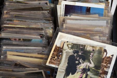 Athen, Griechenland - 21. Mai 2015: Alte Fotos und Vintage-Postkarte Drucke für auf Flohmarkt verkaufen. Junge Paare auf Schwingen mit Blumen geschmückt Romancing.
