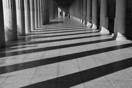 shadow man: ATHENS, GREECE - OCTOBER 14, 2015: Man walking among the columns of stoa attalos at the ancient agora. Light and shadow abstract architecture black and white.