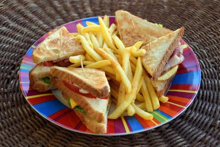 comida chatarra: sándwich club y francés plato de patatas fritas. Fondo de la comida rápida.