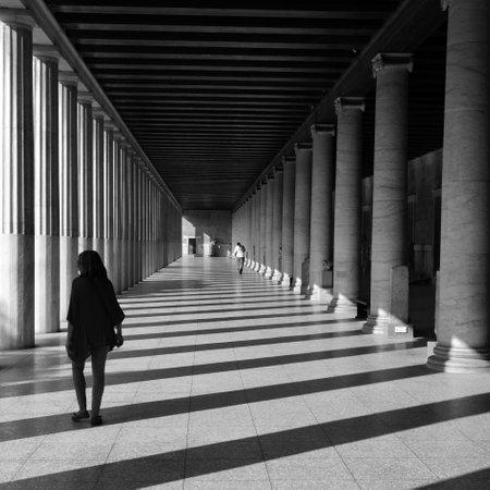 canicas: Atenas, Grecia - 14 de octubre, 2015: La gente en Atalo stoa en la antigua ágora. columnas de luz y sombra a través de Configuración de mármol abstracto blanco y negro. Editorial