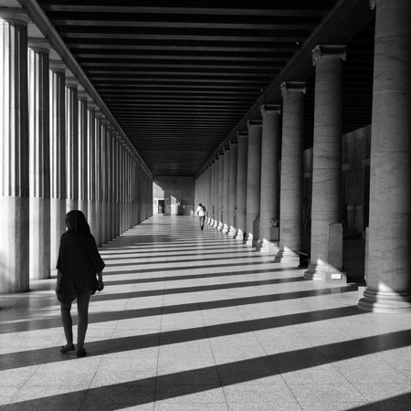 light columns: ATHENS, GREECE - OCTOBER 14, 2015: People in stoa attalos at the ancient agora. Light and shadow through marble columns abstract architecture black and white.