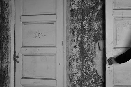 Arm met pop de hand op de deur van een spookhuis. Zwart en wit.