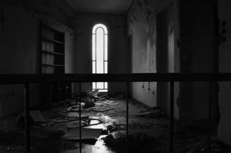 ramshackle: Arched window empty bookcase and dirty floor in abandoned house interior. Black and white.