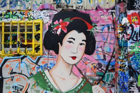 Atenas, Grecia - 10 de diciembre, 2015: Geisha pintada figura femenina japonesa tradicional con el parasol en la pared colorida aerosol pintado. arte de la calle urbana.