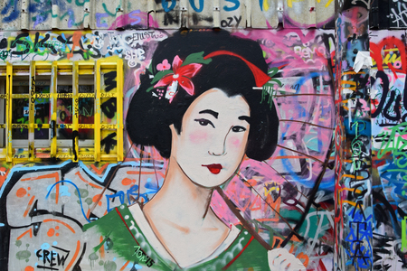 ATHENS, GREECE - DECEMBER 10, 2015: Geisha graffiti traditional japanese female figure with parasol on colorful spray painted wall. Urban street art.
