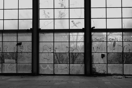 Glass wall broken windows in abandoned gym interior. Black and white.