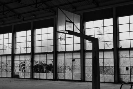 Abandoned basketball court gym interior and glass wall broken windows. Black and white. Foto de archivo