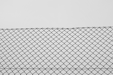 fence wire: Iron chain link fence wire netting with diamond mesh pattern abstract background. Black and white.