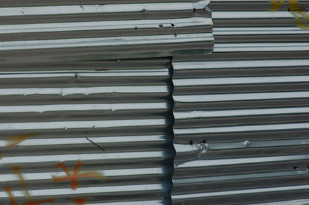 aluminum texture: Construction site fence corrugated aluminum metal sheeting layers. Iron grungy background texture.