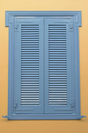 architectural exteriors: Blue window with wooden shutter and yellow wall background. Architectural detail.