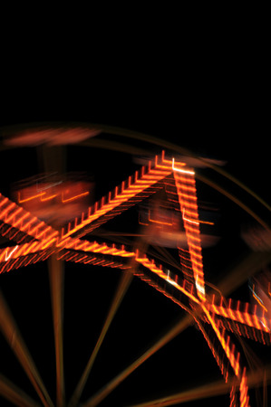 Ferris wheel lights at night abstract motion blur.