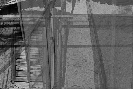 ramshackle: Broken window behind transparent debris netting. Abandoned house black and white.
