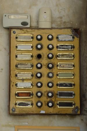 Oud verweerd deurbelpaneel in flatgebouw. Grungy deurbel zoemer met gebroken knoppen. Stockfoto