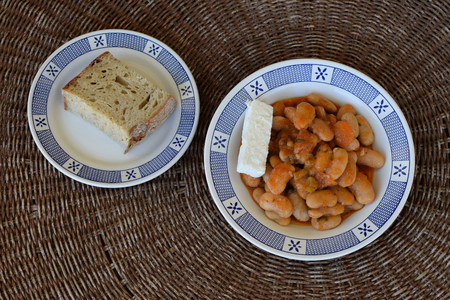 Baked giant beans gigantes with feta cheese and bread. Greek food.