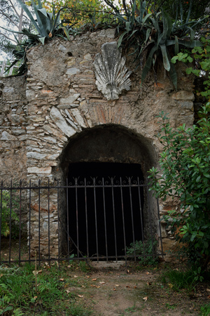 Abandoned wine cellar arched gate with antique acroterion decorative ornament.