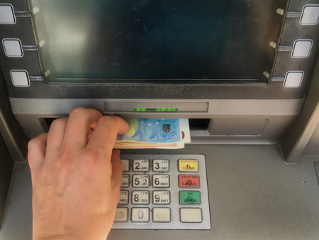 ATHENS, GREECE - AUGUST 5, 2017: Depositor withdraws 420 euro from ATM cash money machine the maximum amount allowed per week by capital controls imposed on banks and accounts. Greek financial crisis.