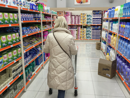 ATHENS, GREECE - JANUARY 20, 2018: Woman shopping at supermarket aisle. Shelves with fabric softener products.