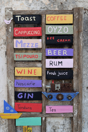 ZAKYNTHOS, GREECE - AUGUST 14, 2018: Wooden cafe bar drinks menu board sign with handmade decorative boats. Editorial