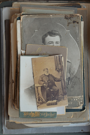 ATHENS, GREECE - SEPTEMBER 14, 2018: Vintage photo of bearded man with cane and footstool. Pile of old photographs and postcards at antiques store.