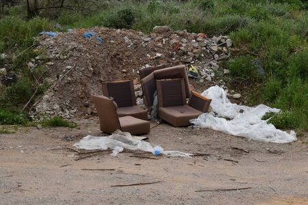 Old armchairs broken furniture and pile of debris rubble and trash by the side of the road. Illegal waste dumping spot.